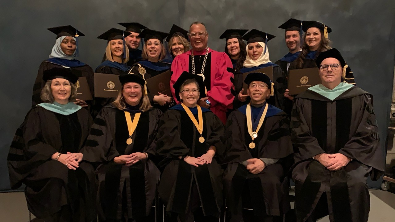 graduates standing with president montgomery