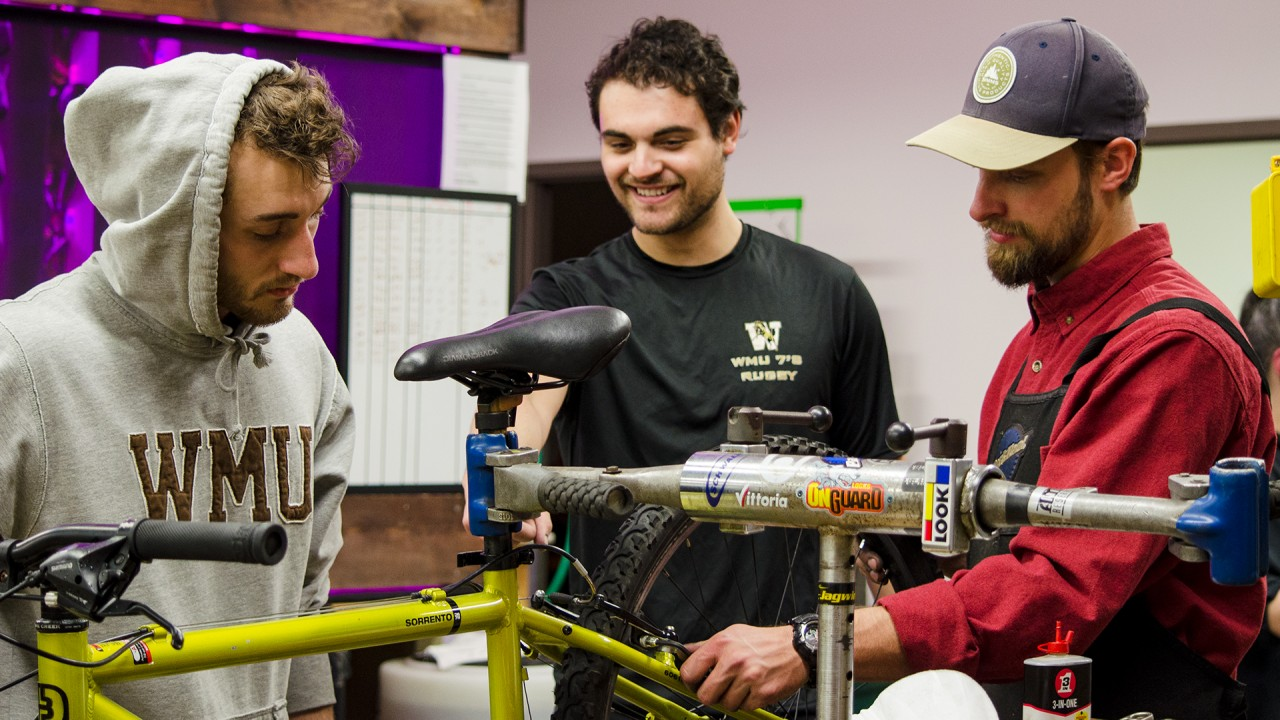 three students gathered around a bike repairing the brakes