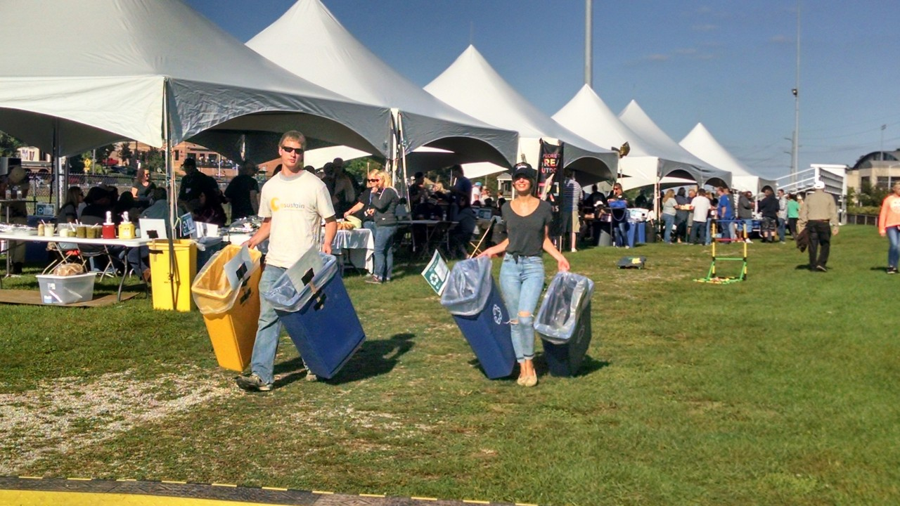 Two volunteers helping carry recycling bins across a lawn during an outdoor event.