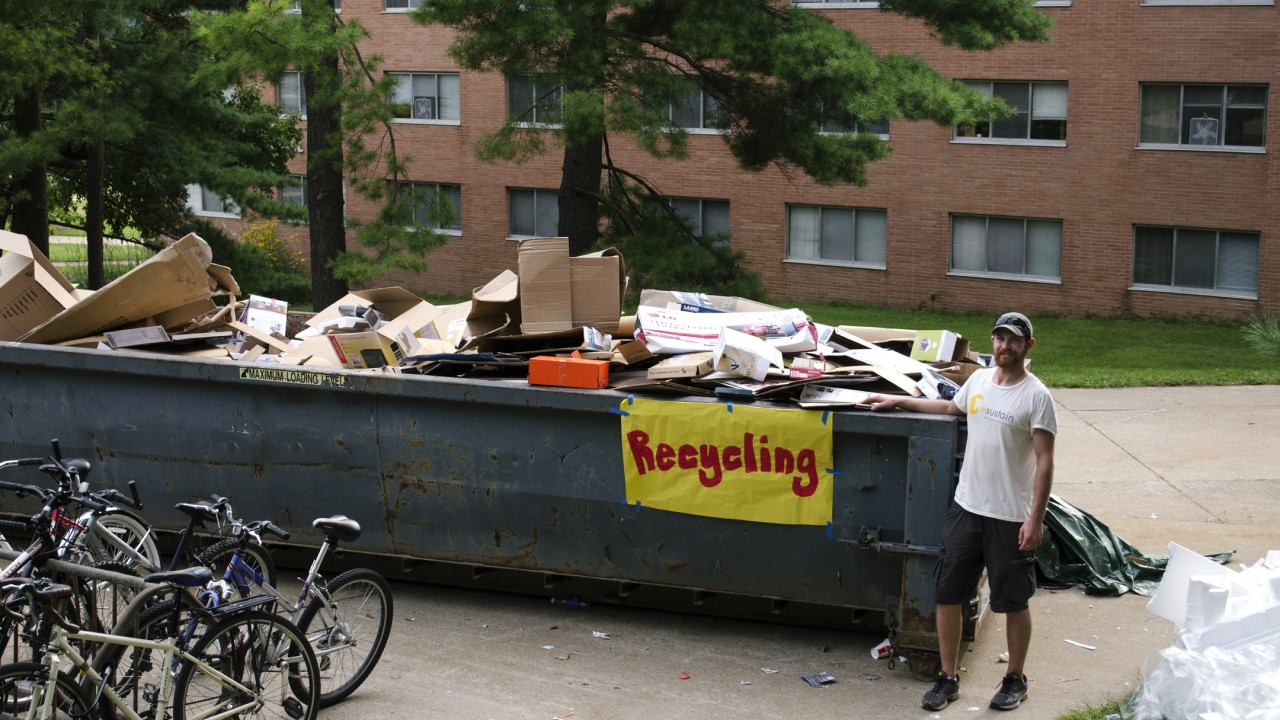 Man standing next to dumpster full of broken down cardboard boxes
