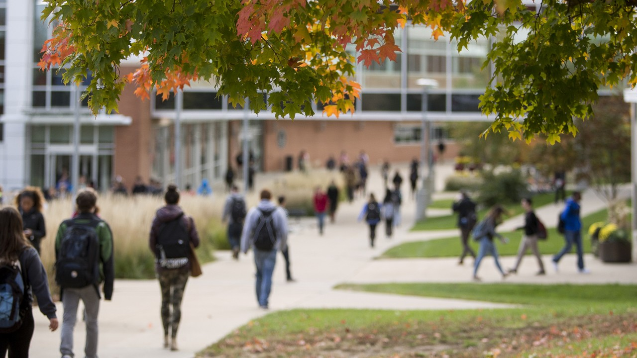 Students walking on campus during the fall season.