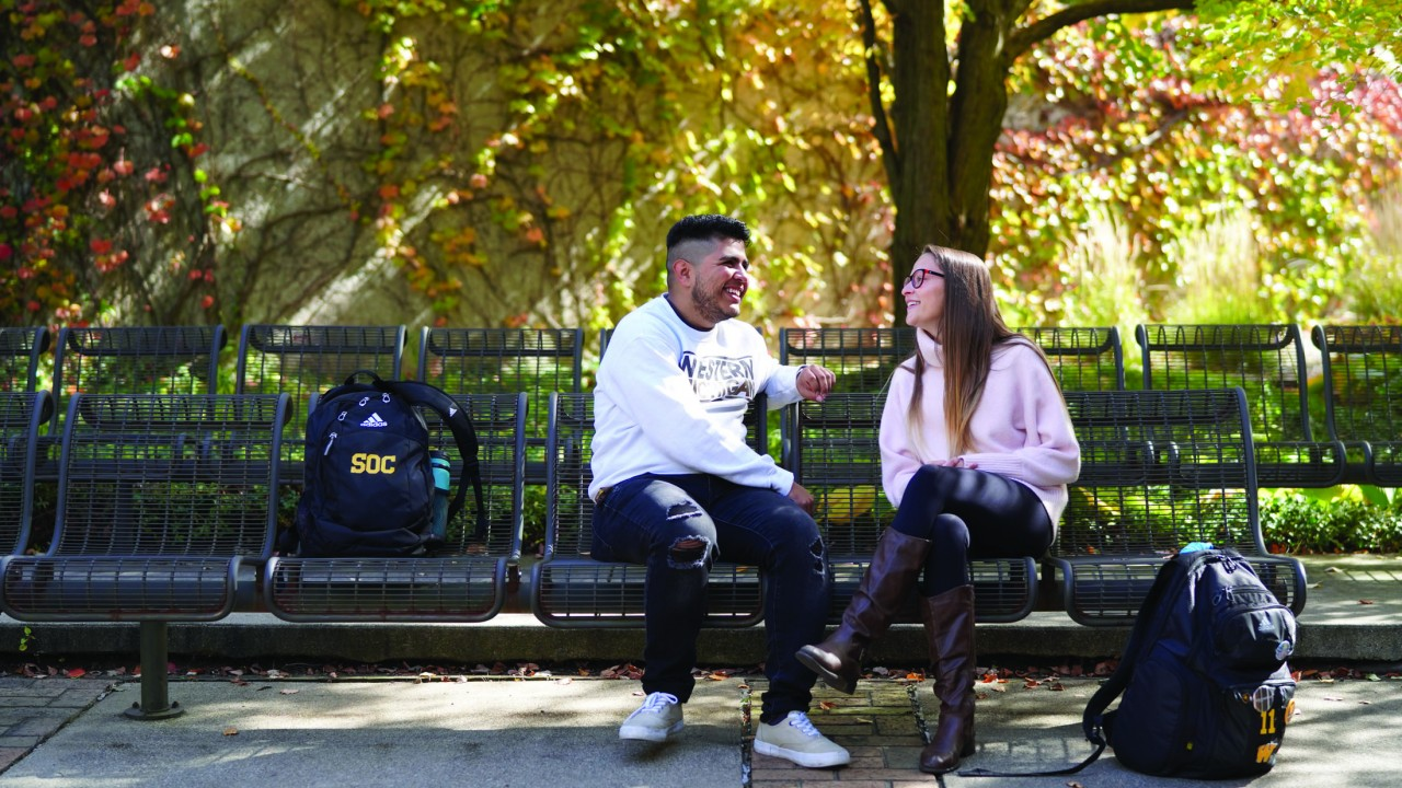 Students on campus on a bench, fall day.