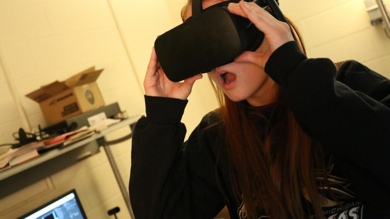 Women with long red hair wearing virtual reality google and a WMU Broncos sweatshirt.