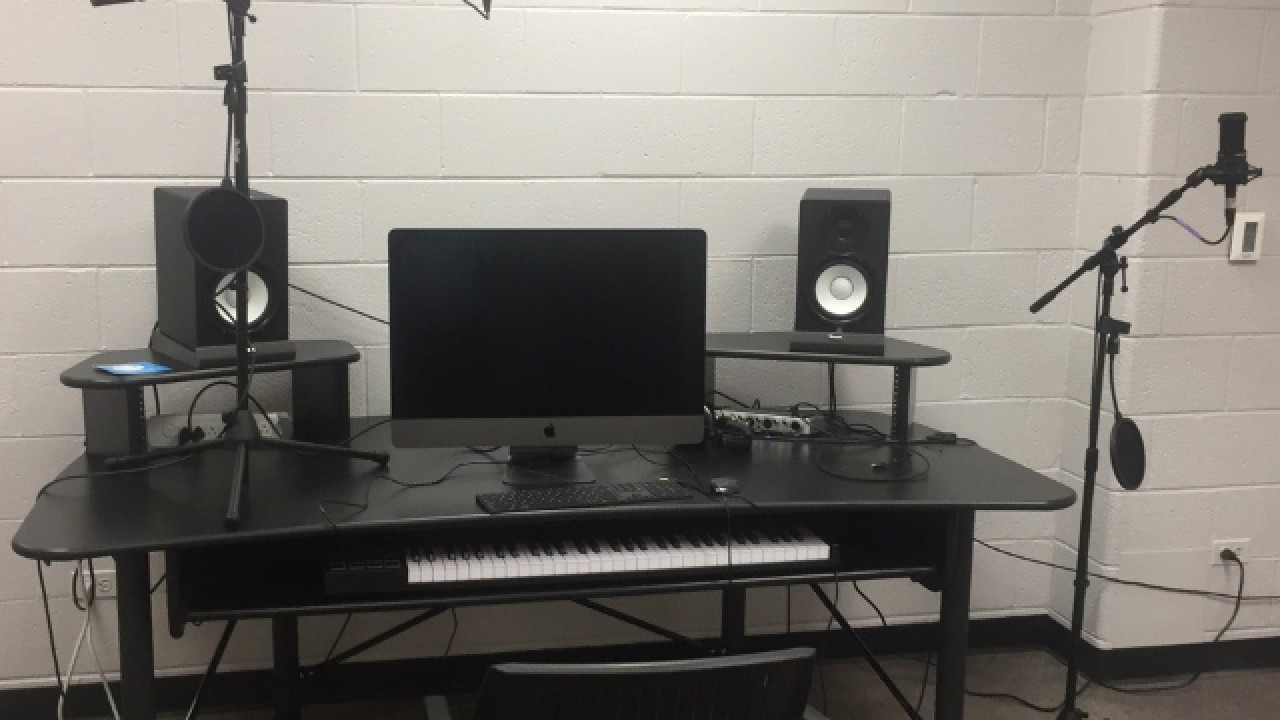 Desk with computer, speakers, music keyboard and two microphones on boom stands.