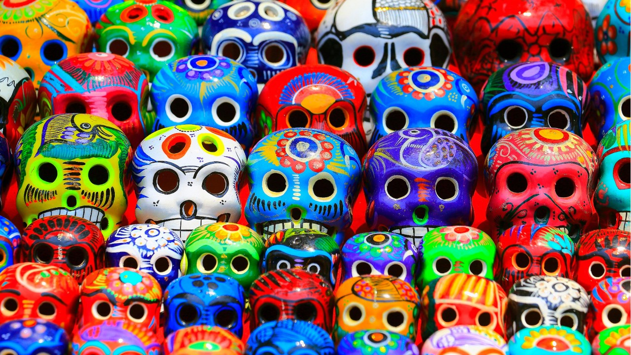 Ceramic skull heads painted in a wide variety of colors and designs.