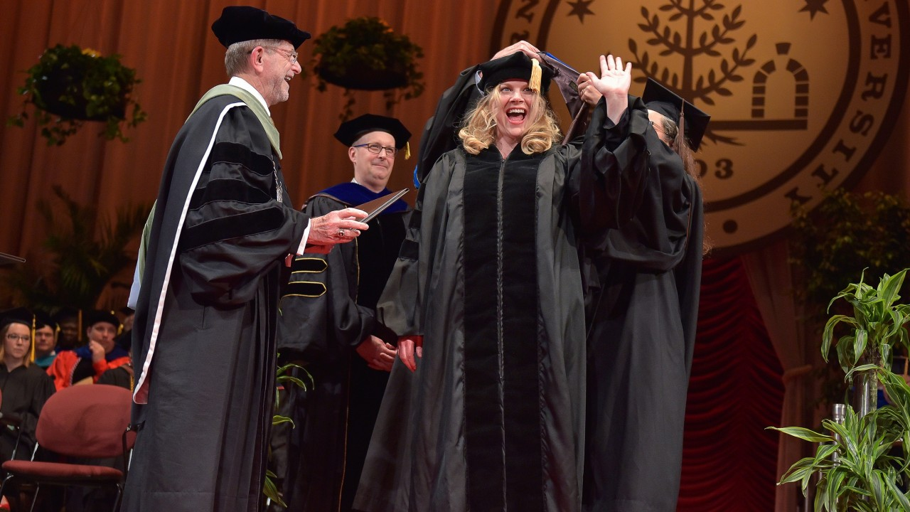 Amy Valentine waves as she receives a Doctor of Philosophy in English