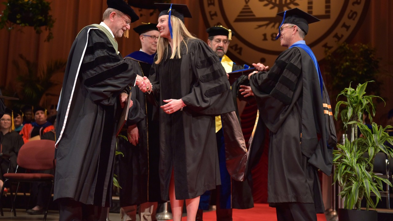 Lindsay Jo Jeffers shakes President Dunn's hand on graduation stage