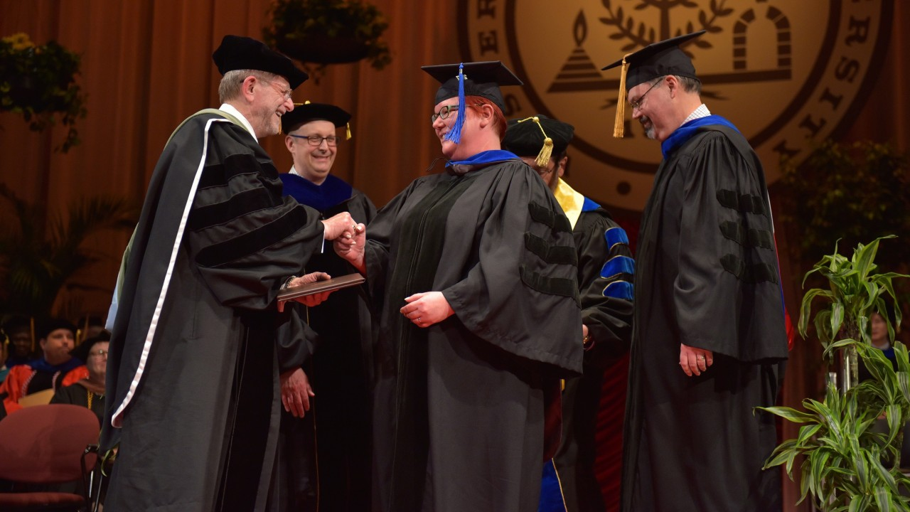 Sarah Perez shakes President Dunn's hands at graduation ceremony
