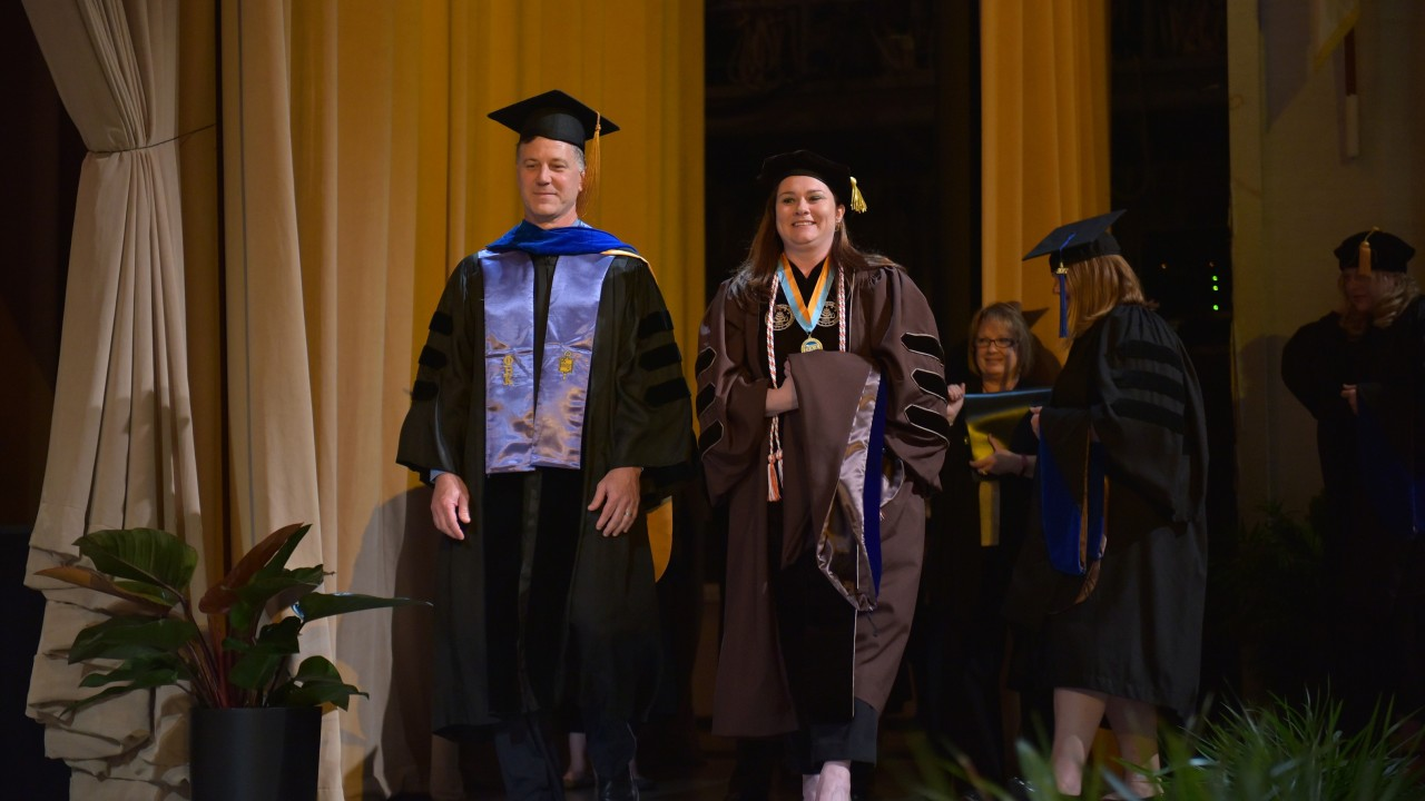 Emma Powell walks across stage to receive doctoral degree