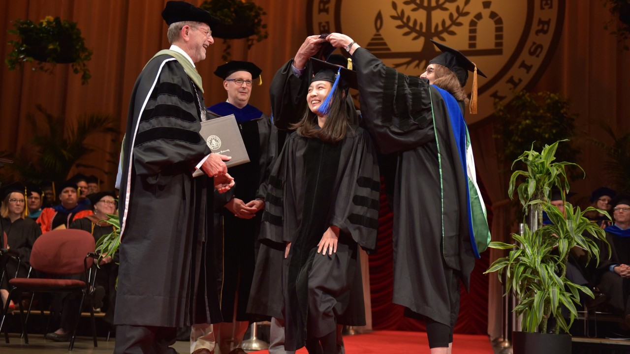 Wan Wei smiles while receiving Ph.D.