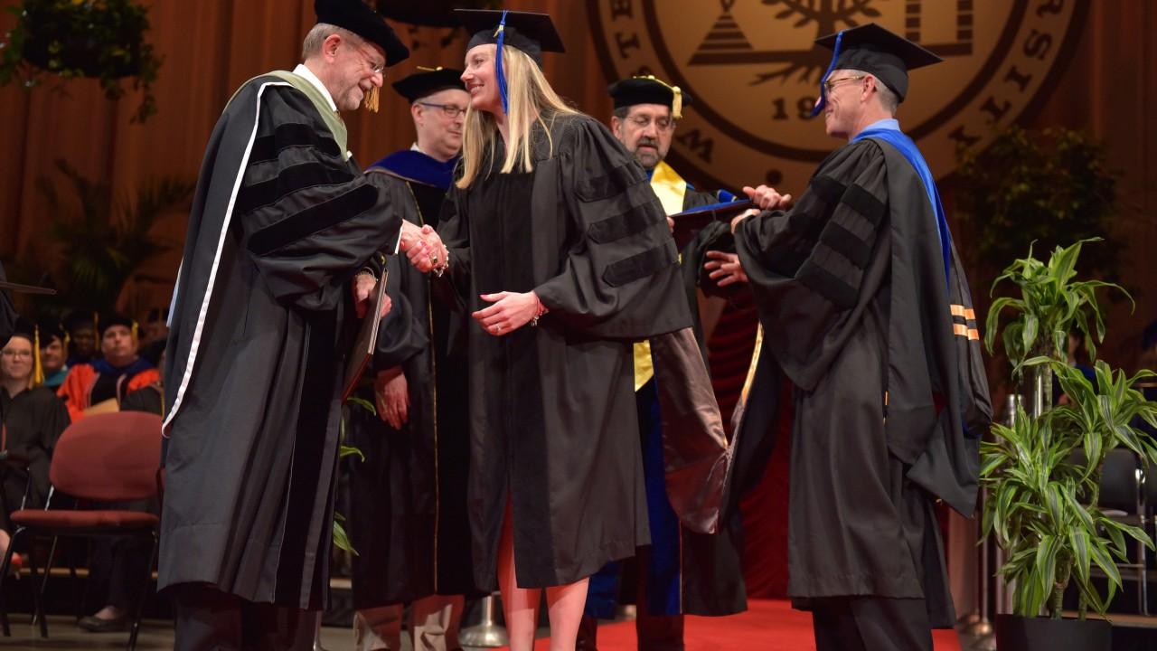 Lindsay Jo Jeffers shakes President Dunn's hand on graduation stage