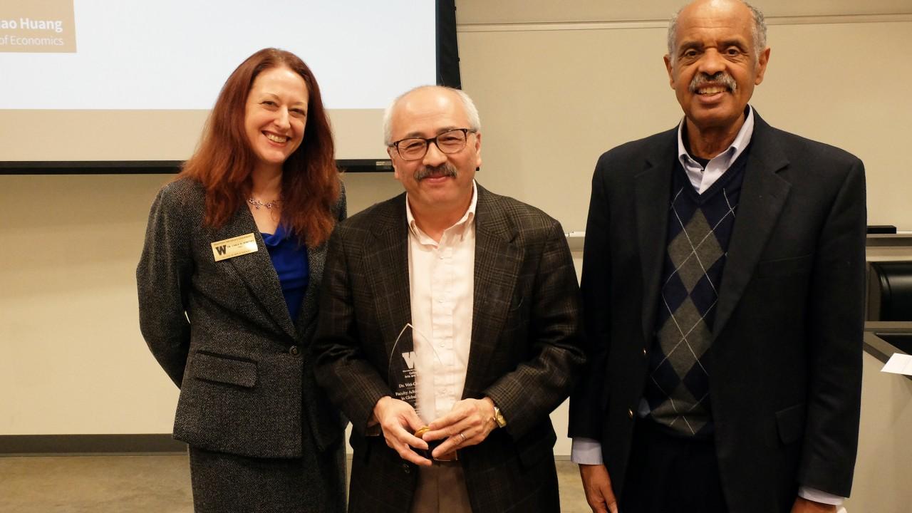 Dr. Carla Koretsky, award winner Dr. Huang (holding plaque) and Dr. Asefa