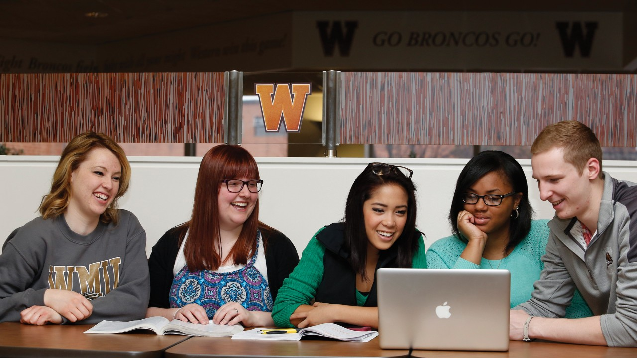 Five students gather around a laptop at a table