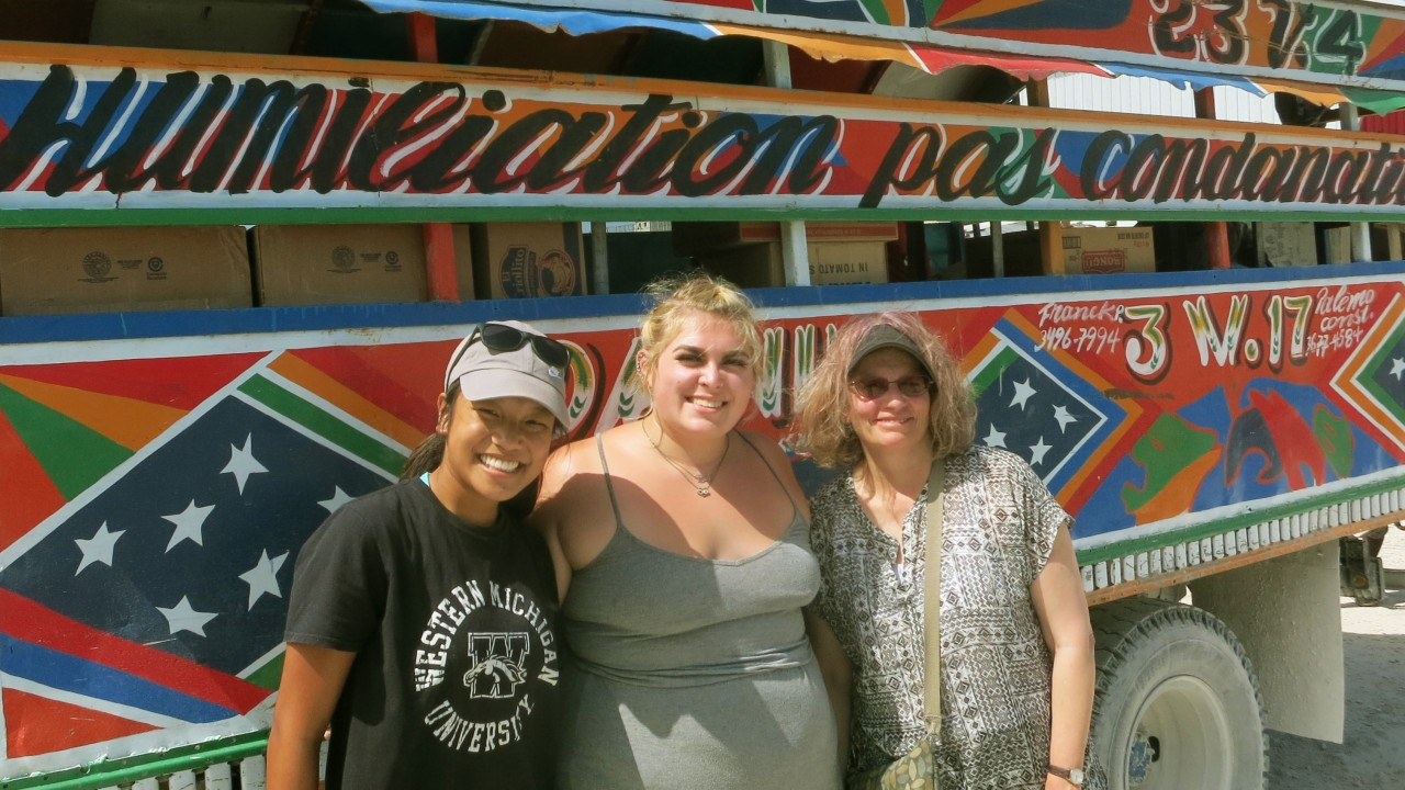 Two students with global and international studies director Dr. Susan Pozo stand in front of a vehicle while studying abroad in the Dominican Republic