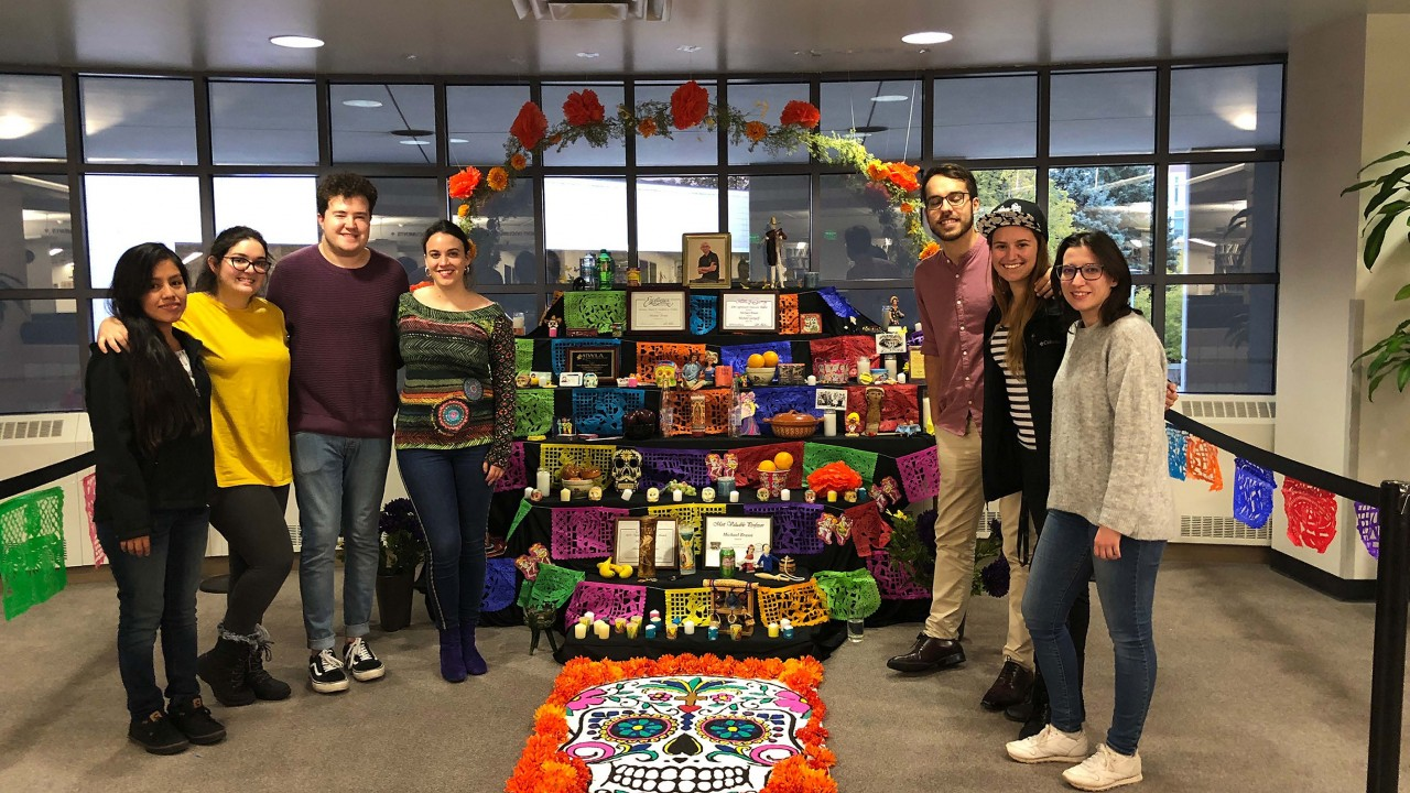 Group of teaching assistants gathered about the Día de los muertos altar