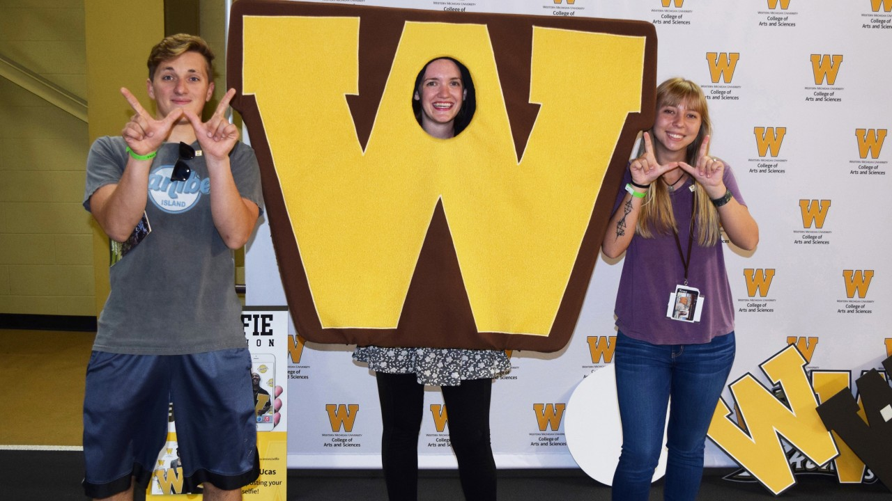 "Students use their fingers to make a ""W"" symbol at a photoshoot at Fall Welcome"