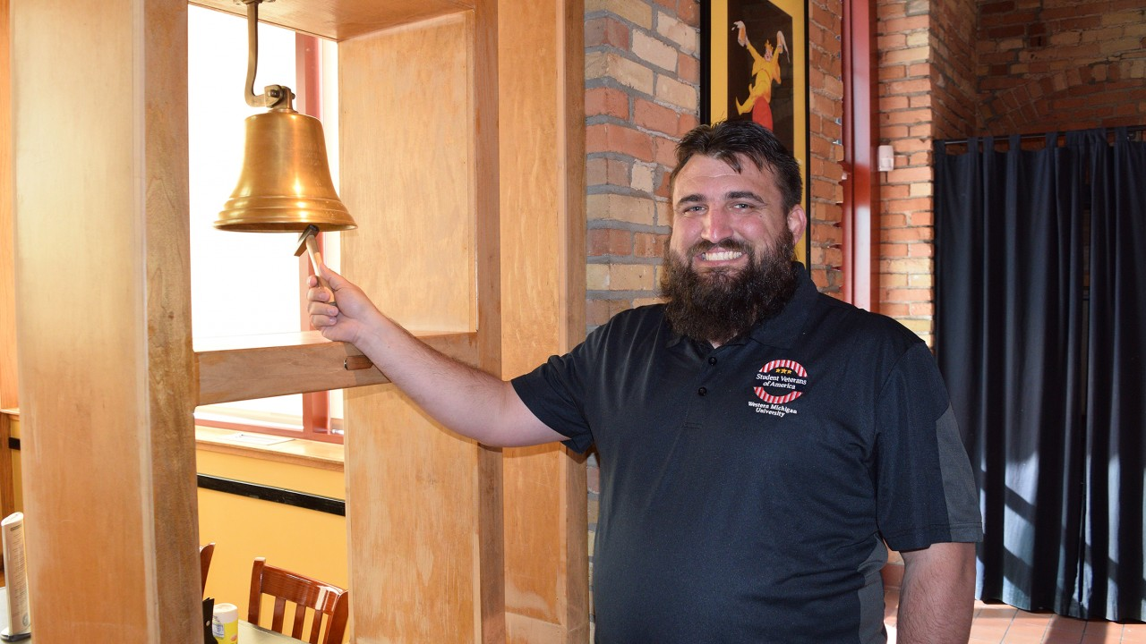 Brad Older rings bell to celebrate his scholarship at the Kalamazoo Beer Exchange