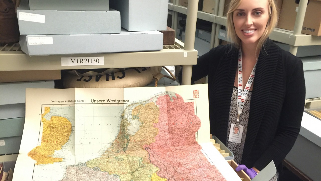 Suzanne Grimmer poses with map of Germany as part of her research project