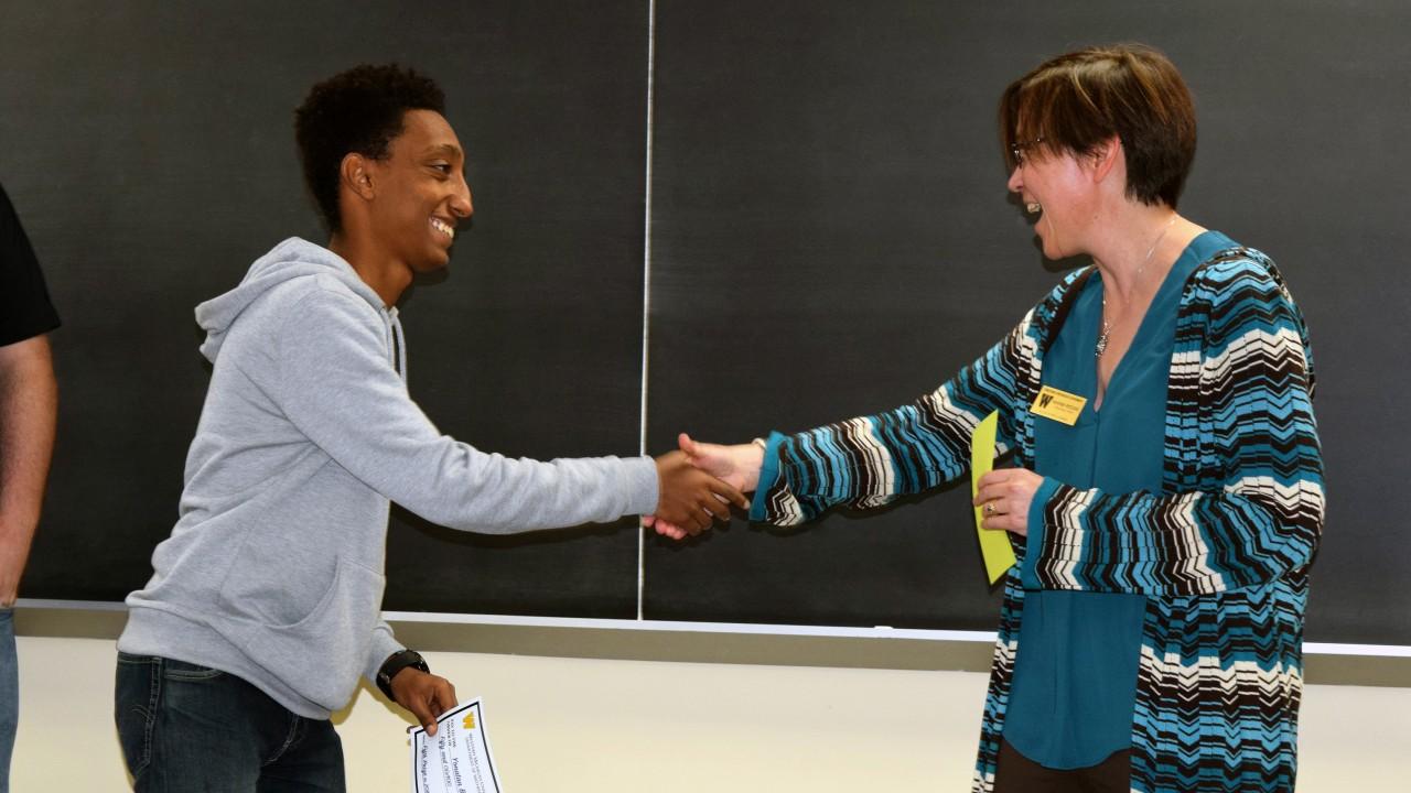 Dr. Heather Petcovic congratulates student Yonatan Beyene, 5th place winner