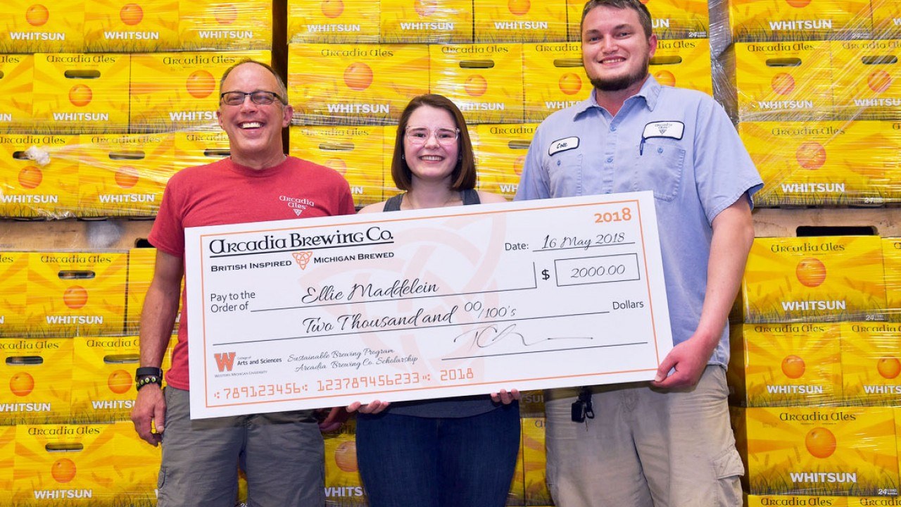 Arcadia owner Tim Suprise stands with scholarship winner Ellie Maddelein and brewer Colton Dykstra