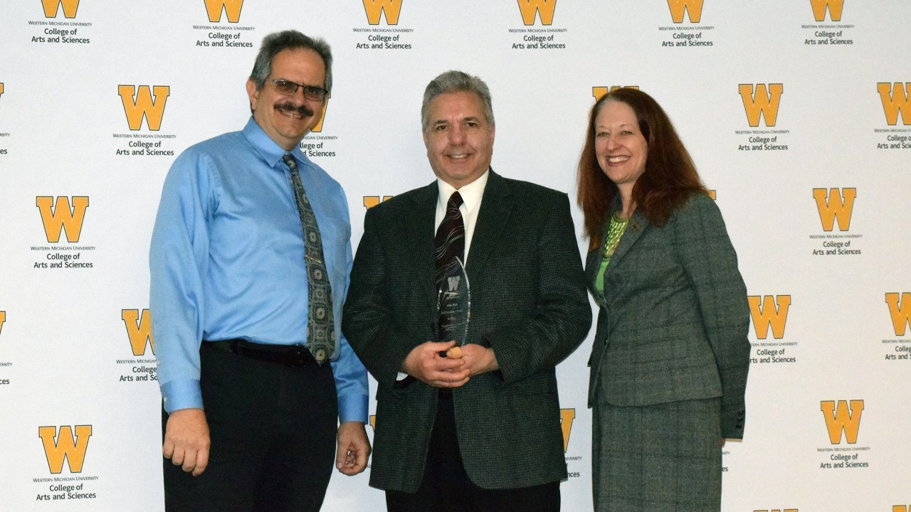 Allan Kern holds plaque while standing with dean Carla Koretsky and physics chair Dr. Paul Pancella