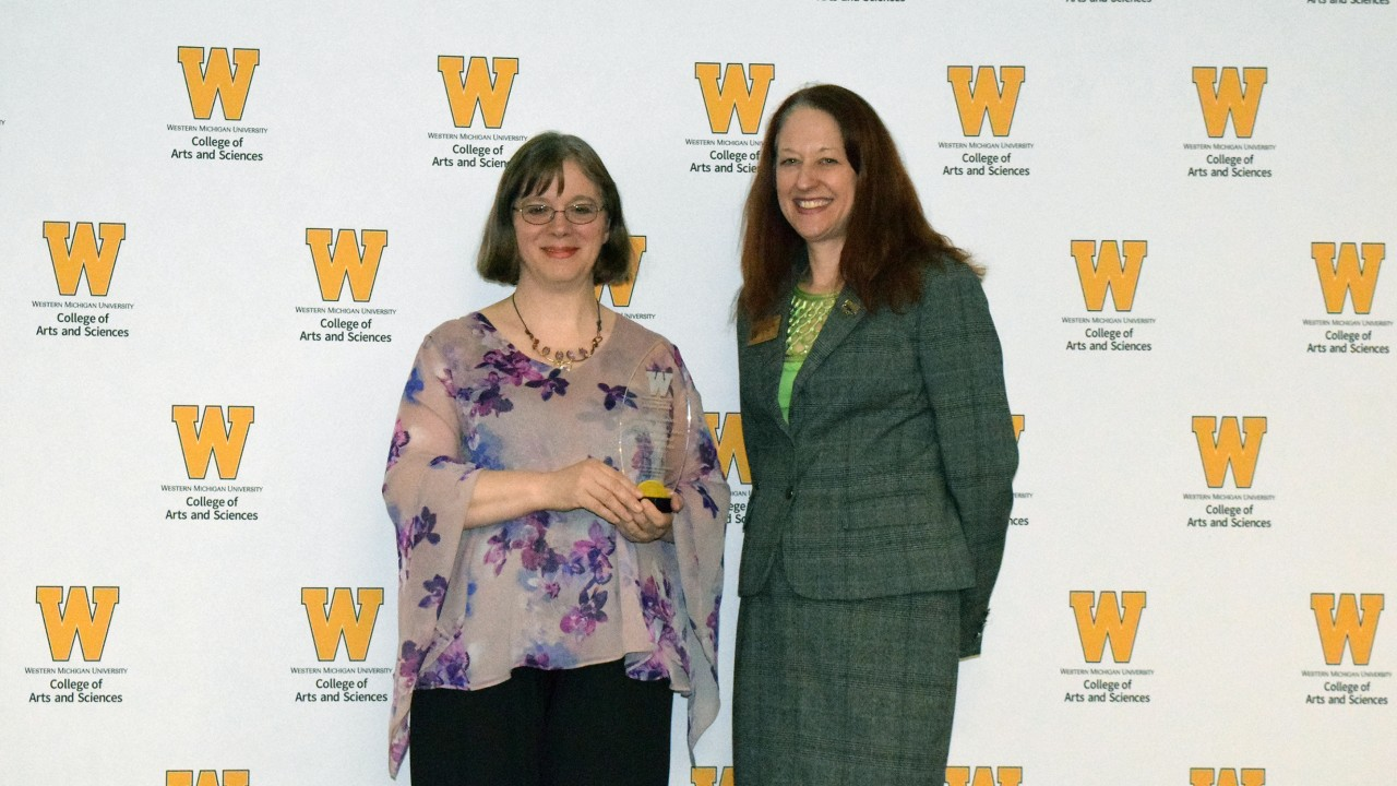 Dr. Sandra Borden holds plaque while standing with dean Carla Koretsky