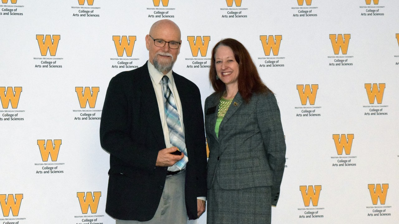 Dr. Lucius Hallett holds plaque while standing with dean Carla Koretsky
