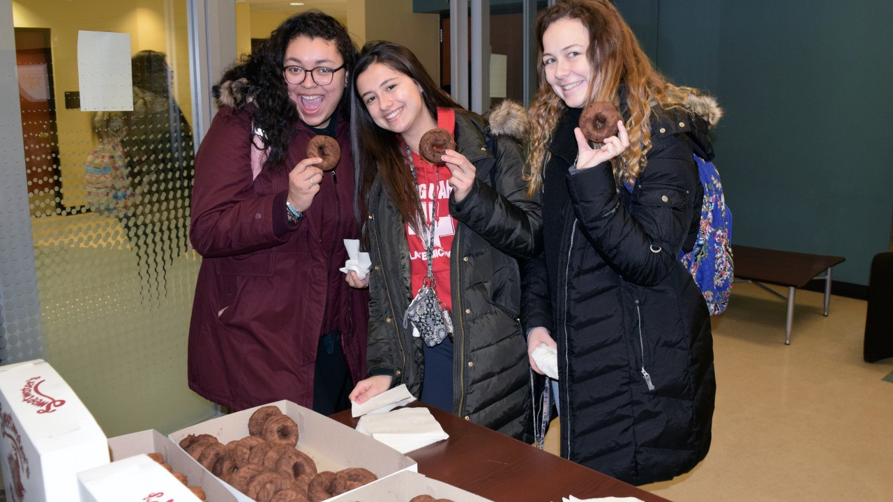 Three female students pose while holding donuts in their hands