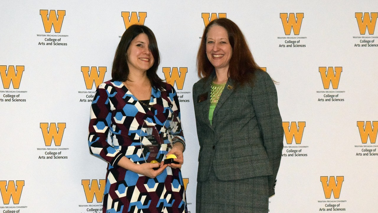 Dr. Alisa Perkins holds plaque while standing with dean Carla Koretsky