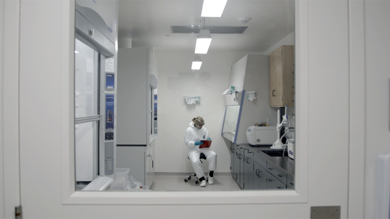A female scientist conducting lab research as seen through a glass door.