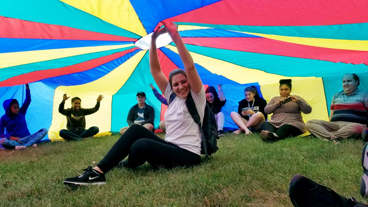 Students sitting under gym class parachute