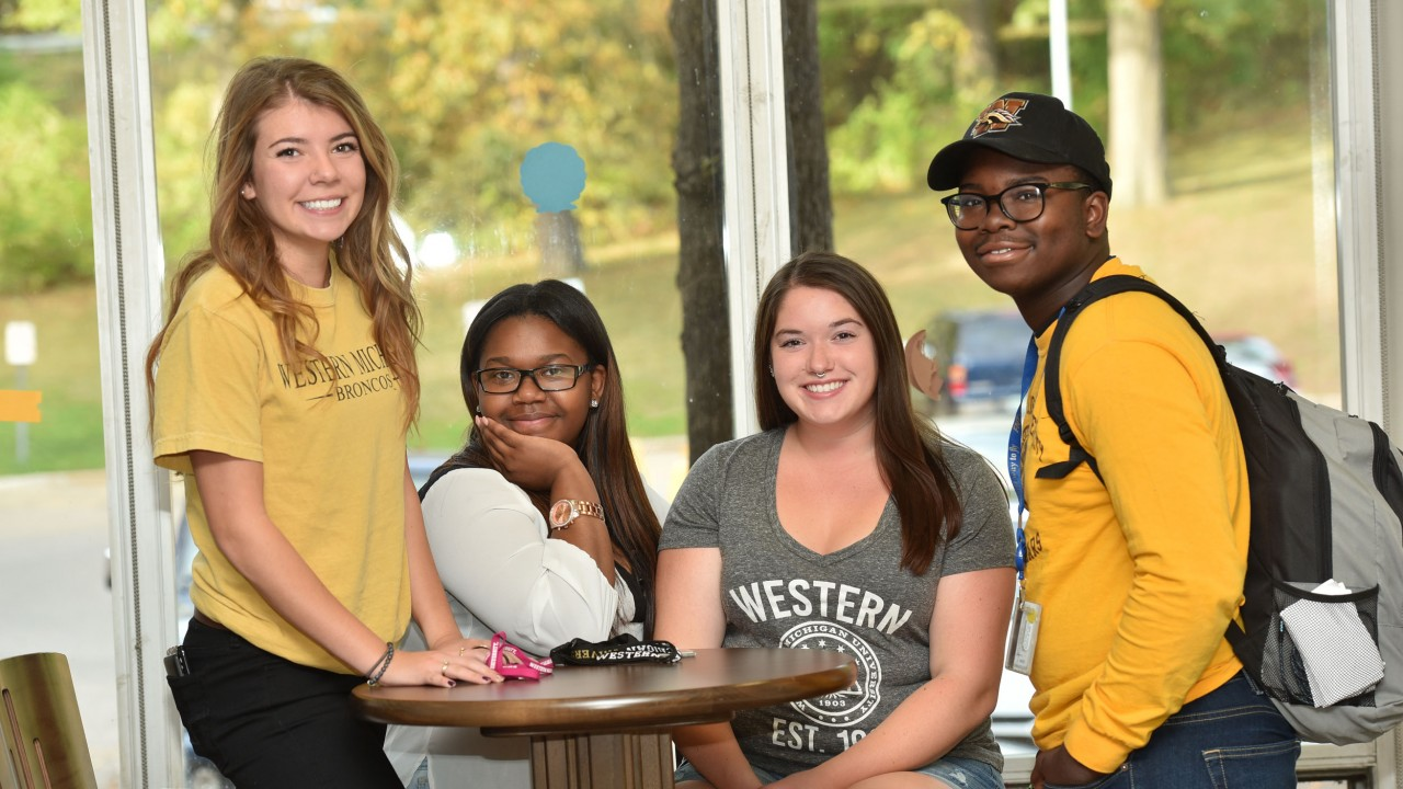 Four students posing at a table in Western Heights