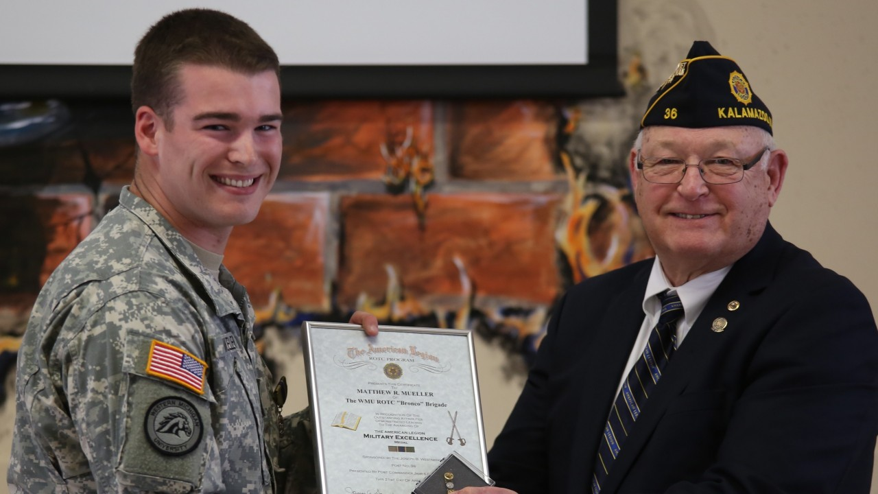 Cadet Mueller receiving an award from the American Legion representative.