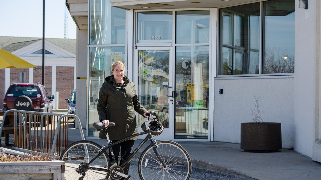 Photo taken on WMU's campus.  A woman stands in front of the office for sustainability with a bike.