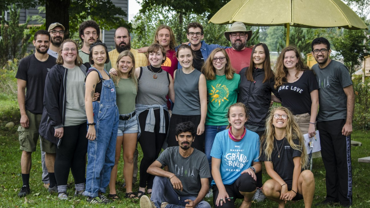 staff photo of office for sustainability. students and staff standing on a green lawn with a yellow umbrella behind, all of the people are smiling