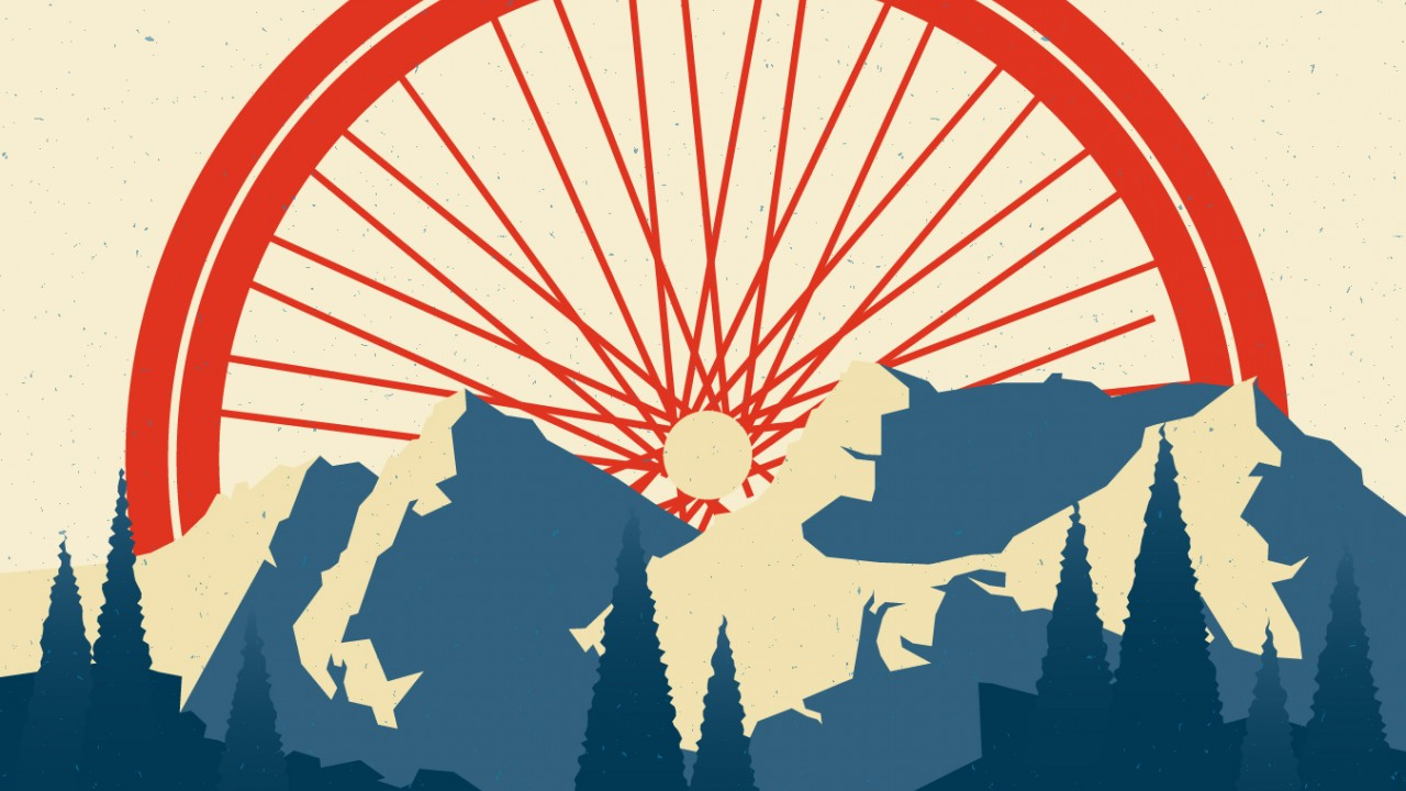 Red bike wheel emerging from mountaintops as if it were the sun