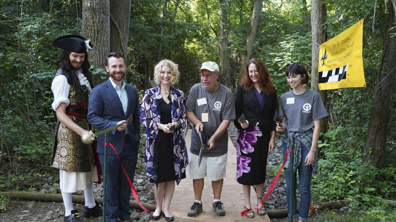 Six people use various tools for an archaeological ribbon cutting ceremony.