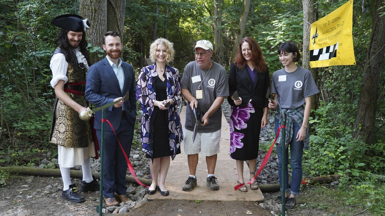 Five people stand with various archaeological tools for a ribbon cutting ceremony.