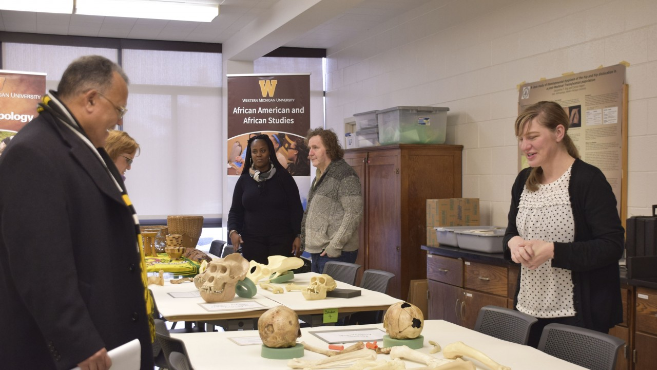 Individuals stand around a table displaying historical artifacts and bones