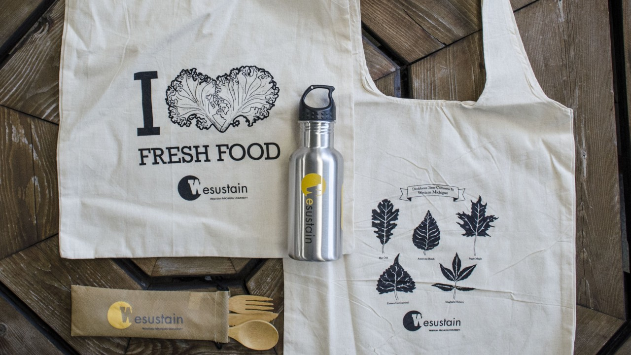 Photo shows EcoEssential items; two canvas tote bags, one EcoJug, and a set of bamboo utensils