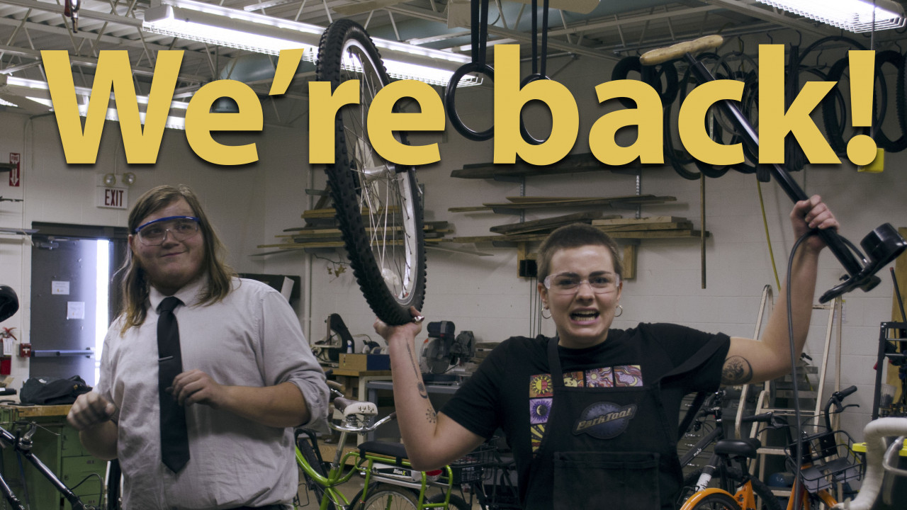 "Text says, ""We're Back"" Image is of two students working in the bike stable. One students is smiling and holding a bike wheel and a bike pump. The other student is smiling in the background"