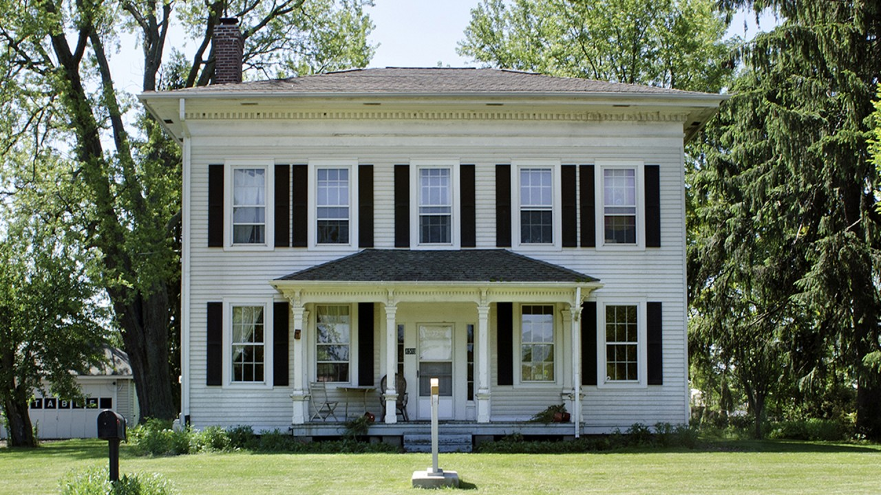 a white, plantation style home on WMU's campus against a backdrop of trees and vegetation
