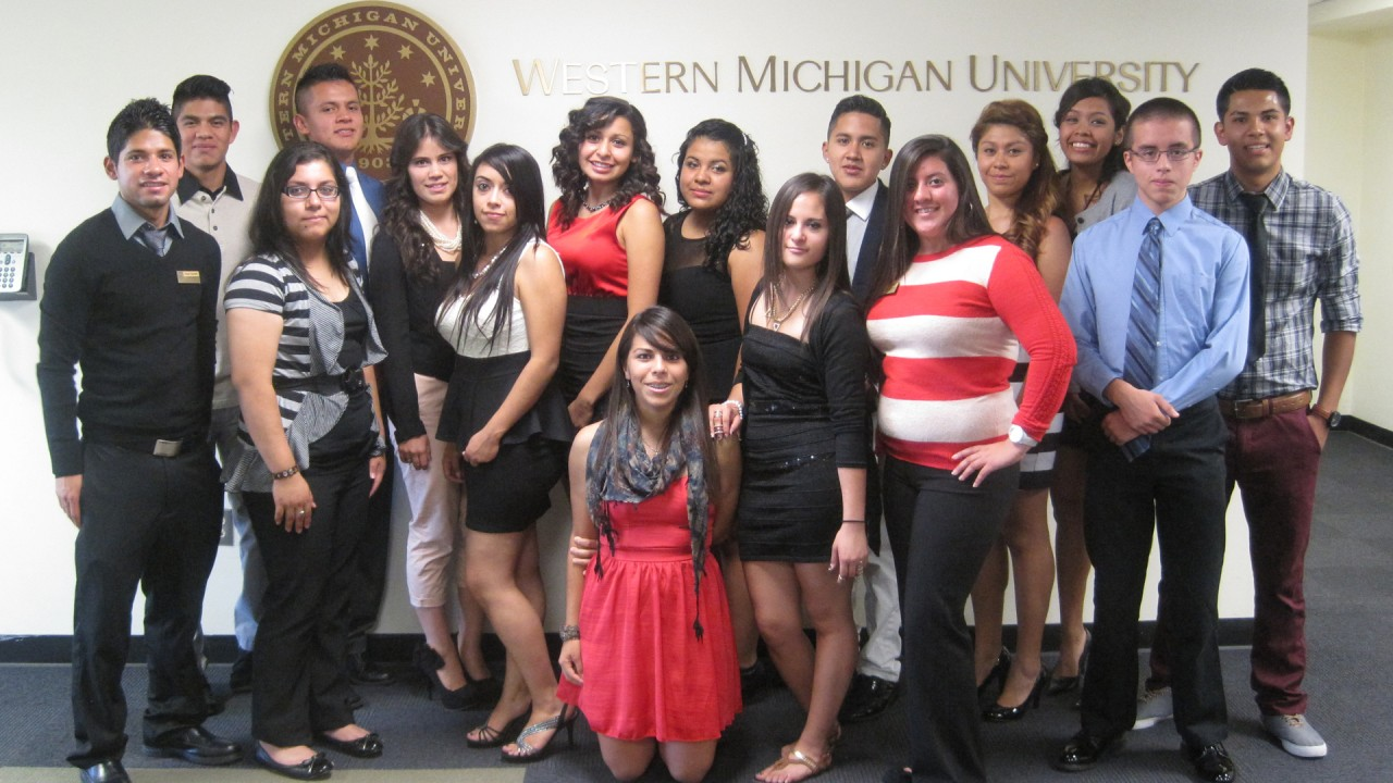 Students posing for a group photo in front of the WMU seal.