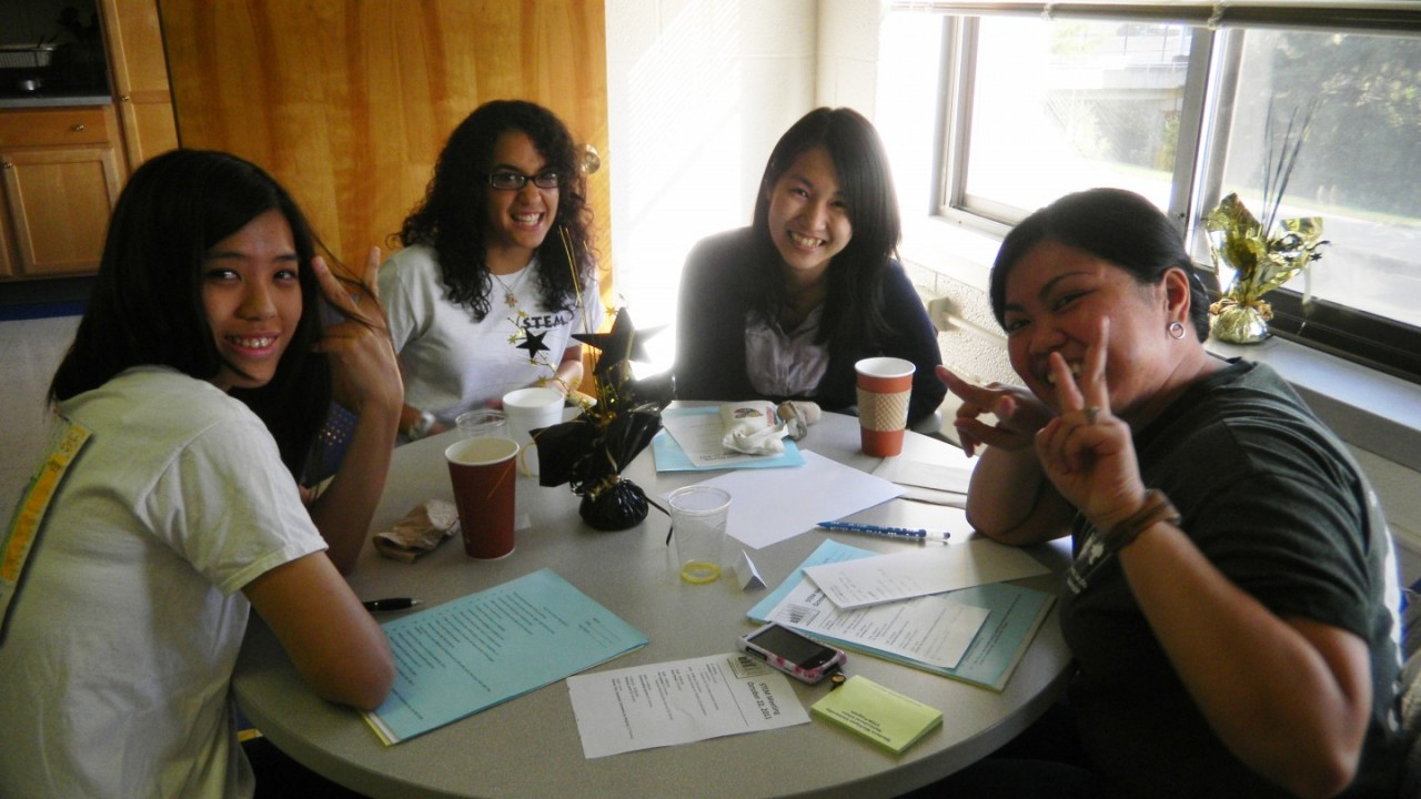 Four peer mentors sitting around the table during a workshop.