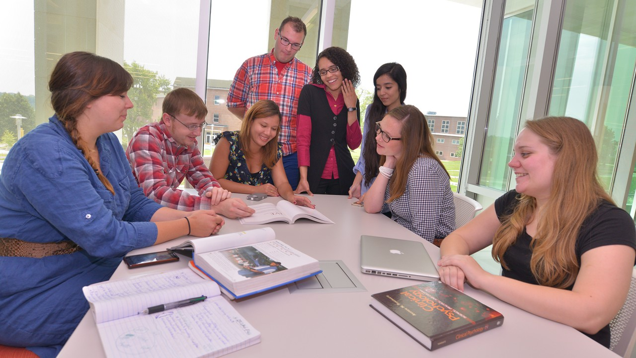 A group of peer mentors gathering around a table during a meeting.