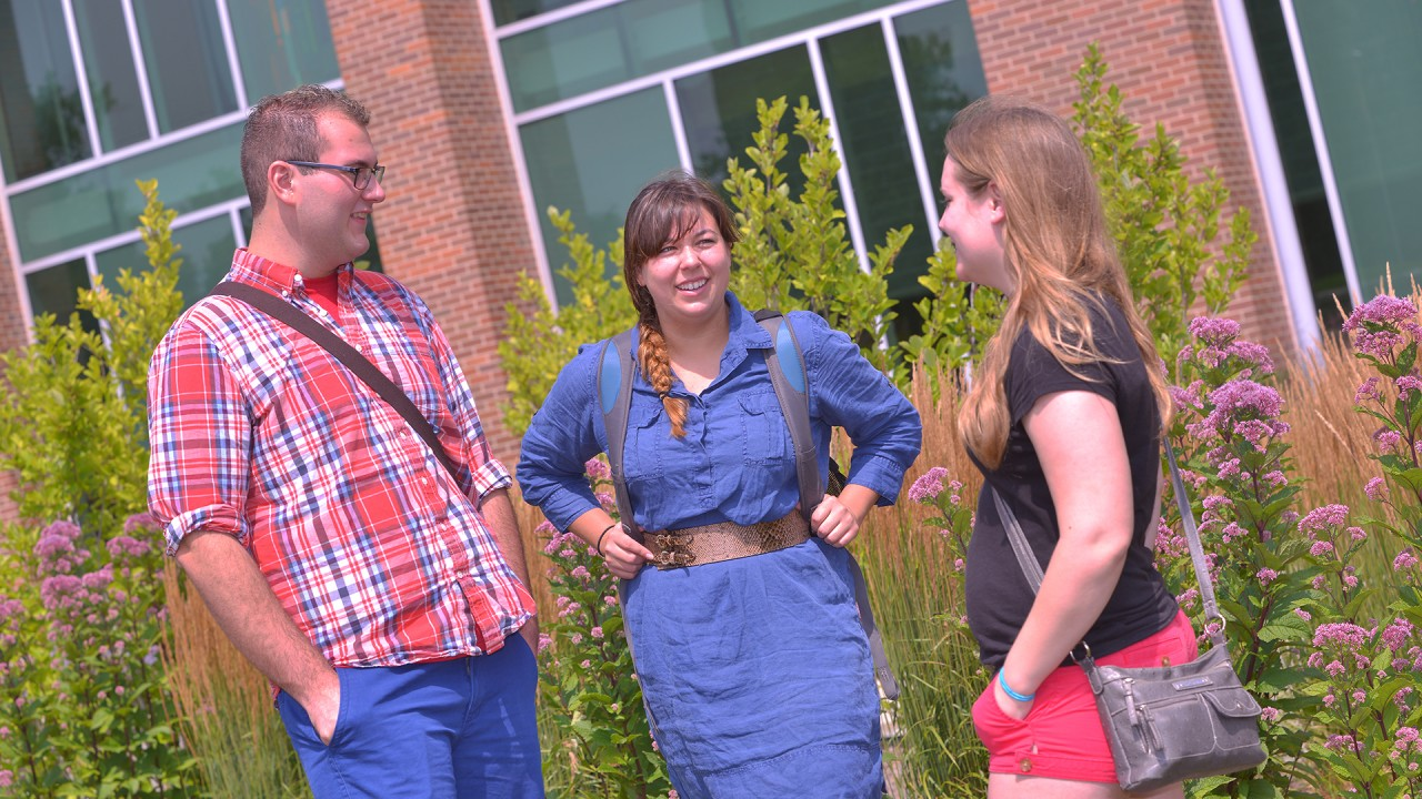 Three participants standing outside a building on campus and having a conversation.