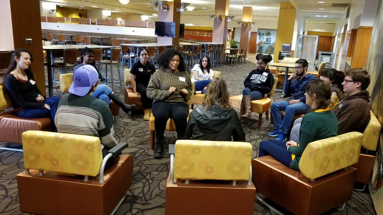 Student employees sitting in a circle for a group activity.