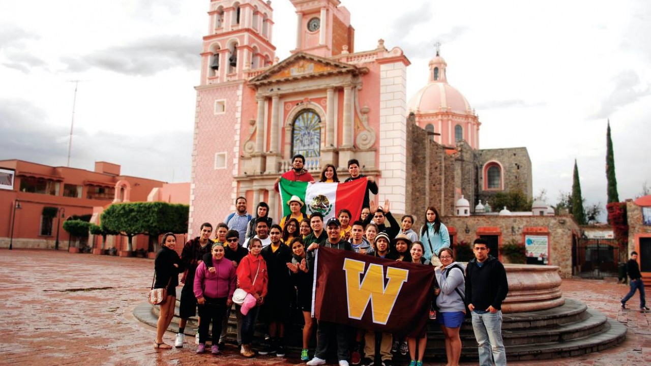 A group of students standing in front of a local landmark holding a WMU flag.