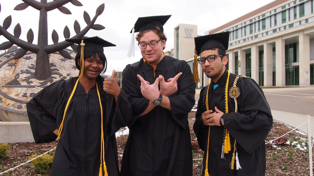 Three student employees in their graduation cap and gown standing in front of Sangren Hall.