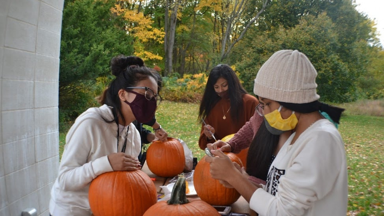 A group of students carving and painting pumpkins.